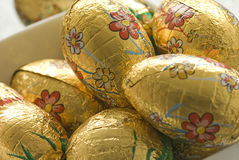 Easter eggs in aluminum foil. A close up view of a number of easter eggs wrapped in decorative gold aluminum or tin foil royalty free stock photography