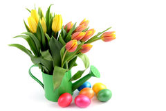 Easter eggs around water can vase with Tulips Royalty Free Stock Photos