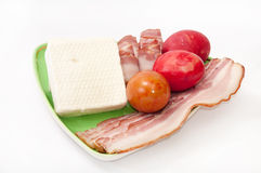Easter eggs and arranged bacon and feta cheese on a green plate Stock Images