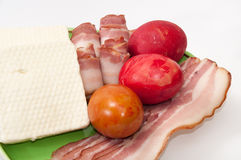 Easter eggs and arranged bacon and feta cheese on a green plate Stock Image