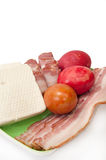 Easter eggs and arranged bacon and feta cheese on a green plate Royalty Free Stock Images