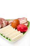 Easter eggs and arranged bacon and feta cheese on a green plate Royalty Free Stock Photos