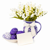 Easter eggs and artificial lily of the valley flowers on white b Stock Photo