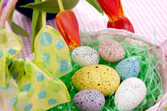 Easter eggs in a Basket. Easter Painted Colorful eggs in pink basket decorated with spring tulips on a pastel background Stock Photography