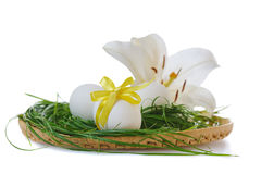 Easter eggs in basket. With white lily  on white background Royalty Free Stock Image