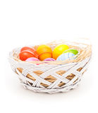 Easter eggs in the basket. Colorful Easter eggs. Hand painted colorful Easter eggs arranged with natural hay and  on white background Stock Images