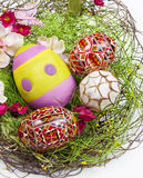 Easter eggs in basket. With straw on white background Stock Photos