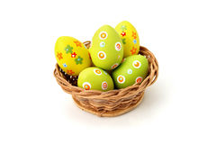Easter eggs in a basket. Wicker basket with Easter eggs on white background Stock Photo