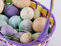 Easter Eggs in a basket. Multi colored pastel speckled eggs in an Easter basket with Easter grass Stock Photos