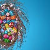 Easter Eggs basket arrangement on blue. Colorful wooden Easter Eggs in a floral basket on blue background Royalty Free Stock Photography