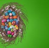 Easter Eggs basket arrangement on green. Colorful wooden Easter Eggs in a floral basket on green background Stock Images