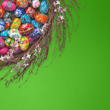 Easter Eggs basket arrangement on green. Colorful wooden Easter Eggs in a floral basket set on green background Royalty Free Stock Images