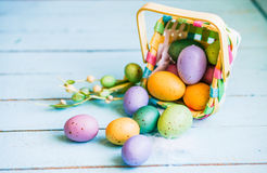 Easter eggs in the basket on blue wooden background Stock Photos