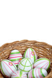 Easter eggs in a basket from bottom. Wicker basket with Easter eggs isolated on white background Stock Images