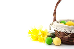 Easter eggs in the basket with bouquet of yellow daffodil Royalty Free Stock Photography