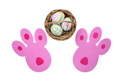 Easter eggs in a basket and bunny tracks top view Royalty Free Stock Photos