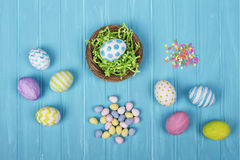Easter eggs, basket, and candy on a blue background Stock Photography