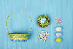 Easter eggs, basket, and candy on a blue background Royalty Free Stock Image