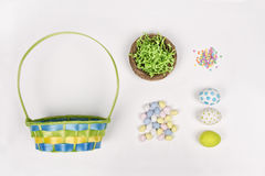 Easter eggs, basket, and candy on a white background Stock Images
