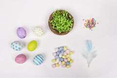Easter eggs, basket, and candy on a white background Stock Image