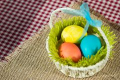 Easter eggs in a basket on a canvas napkin royalty free stock photos