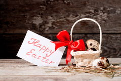 Easter eggs in a basket with a card happy easter Royalty Free Stock Images
