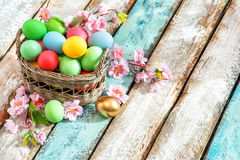 Easter eggs basket colorful decoration flowers. Easter eggs in basket on rustic wooden background. Colorful decoration with flowers on sunny day Royalty Free Stock Photography