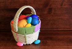 Easter Eggs and Basket. Colourful dyed and Candy  Easter eggs in a weaved basket with a wood background Stock Images