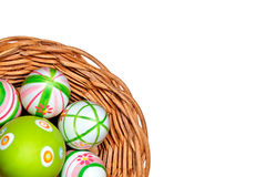 Easter eggs in a basket from corner. Isolated on white background Royalty Free Stock Image