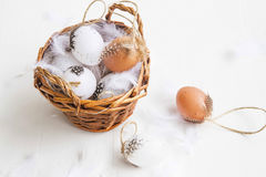 Easter eggs basket decorated with feathers on white painted wood Stock Photo