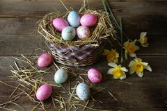 Easter eggs in a basket decorated with straw and narcissus on a wooden rustic background stock photos