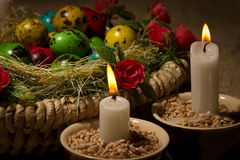 Easter eggs in basket with Easter candles Stock Images