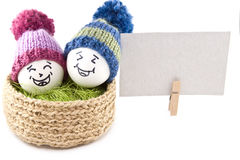Easter eggs in a basket. Emoticons in knitted hats with pom-poms Stock Photos