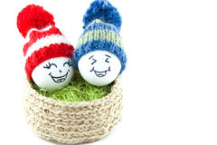 Easter eggs in a basket. Emoticons in knitted hats with pom-poms Royalty Free Stock Photos