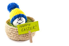 Easter eggs in a basket. Emoticons in knitted hats with pom-poms Royalty Free Stock Photo