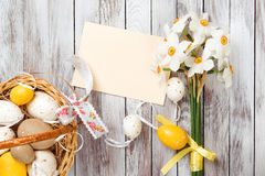 Easter eggs in basket, empty greeting card, bouquet of daffodils on wooden background. Easter decorations. Royalty Free Stock Image