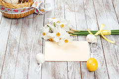 Easter eggs in basket, empty greeting card, bouquet of daffodils on wooden background. Easter decorations. royalty free stock photos