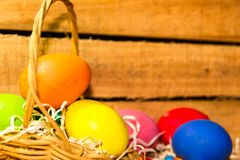 Easter eggs in the basket on the farm with wooden rustic background stock image