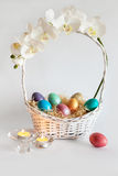 Easter eggs in the basket with flowers and candles Stock Photos