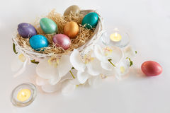 Easter eggs in basket with flowers and candles Royalty Free Stock Photo