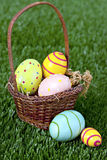 Easter eggs and basket in grass Royalty Free Stock Photos