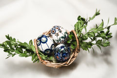 Easter eggs in basket and green twigs. Stock Photography