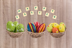Easter eggs in a basket . Easter eggs in a basket with a happy wishes Stock Images