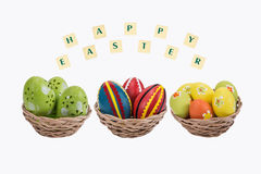 Easter eggs in a basket . Easter eggs in a basket with a happy wishes on white background Royalty Free Stock Images