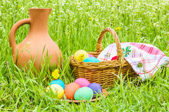 Easter eggs, basket, a jug in the grass Stock Image