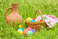 Easter eggs, basket and a jug in the grass Royalty Free Stock Photography