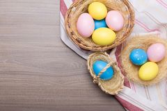 Easter eggs in the basket with kitchen towel on wooden background stock photos