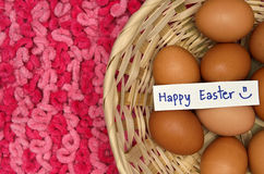 Easter eggs in basket with note on pink fabric background Stock Image