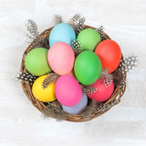 Easter eggs in basket over bright wooden background Stock Photo