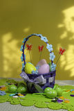 Easter eggs basket. Painted eggs. Easter background. Easter theme decoration. Colorful easter eggs on yellow background Royalty Free Stock Photo